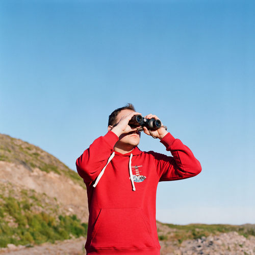 Man photographing against clear blue sky