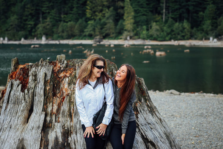 Mother and daughter leaning on large tree stump by lake