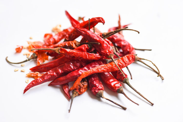 Close-up of red chili peppers over white background