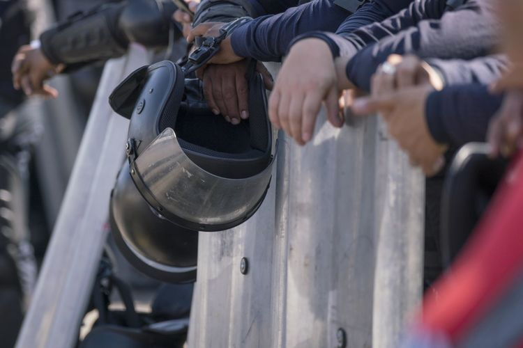 An anti-riot policeman holds his helmet during an operation. Activity Aggression  Body Part Close-up Day Hand Helmet Holding Human Body Part Human Hand Human Leg Human Limb Low Section Men Midsection Motion Nature Outdoors People Real People Selective Focus Strength Two People