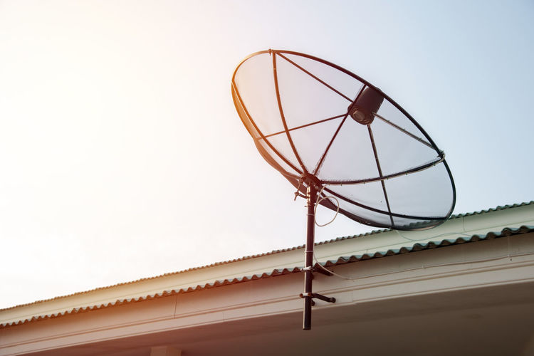 Low angle view of antenna on roof against clear sky