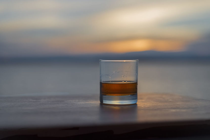 Hero whiskey solo on table by the sea Al Fresco Alcohol Bourbon Cruise Dram Drink Focus On Foreground Gambling Glass Golden HERO Liquor Masculine No People Ocean Outside Refreshment Sailing Scotch Sea Selective Focus Solo Sunset Whiskey