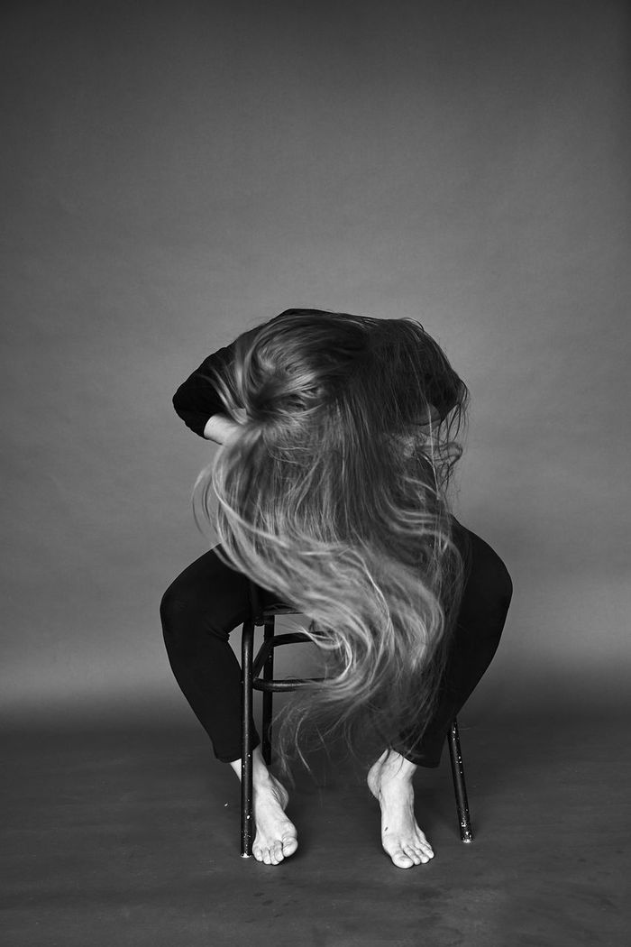 Woman covering her face by hair while sitting on chair against gray background