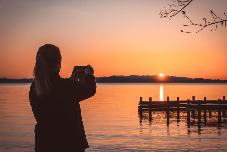 Rear view of woman photographing lake against orange sky