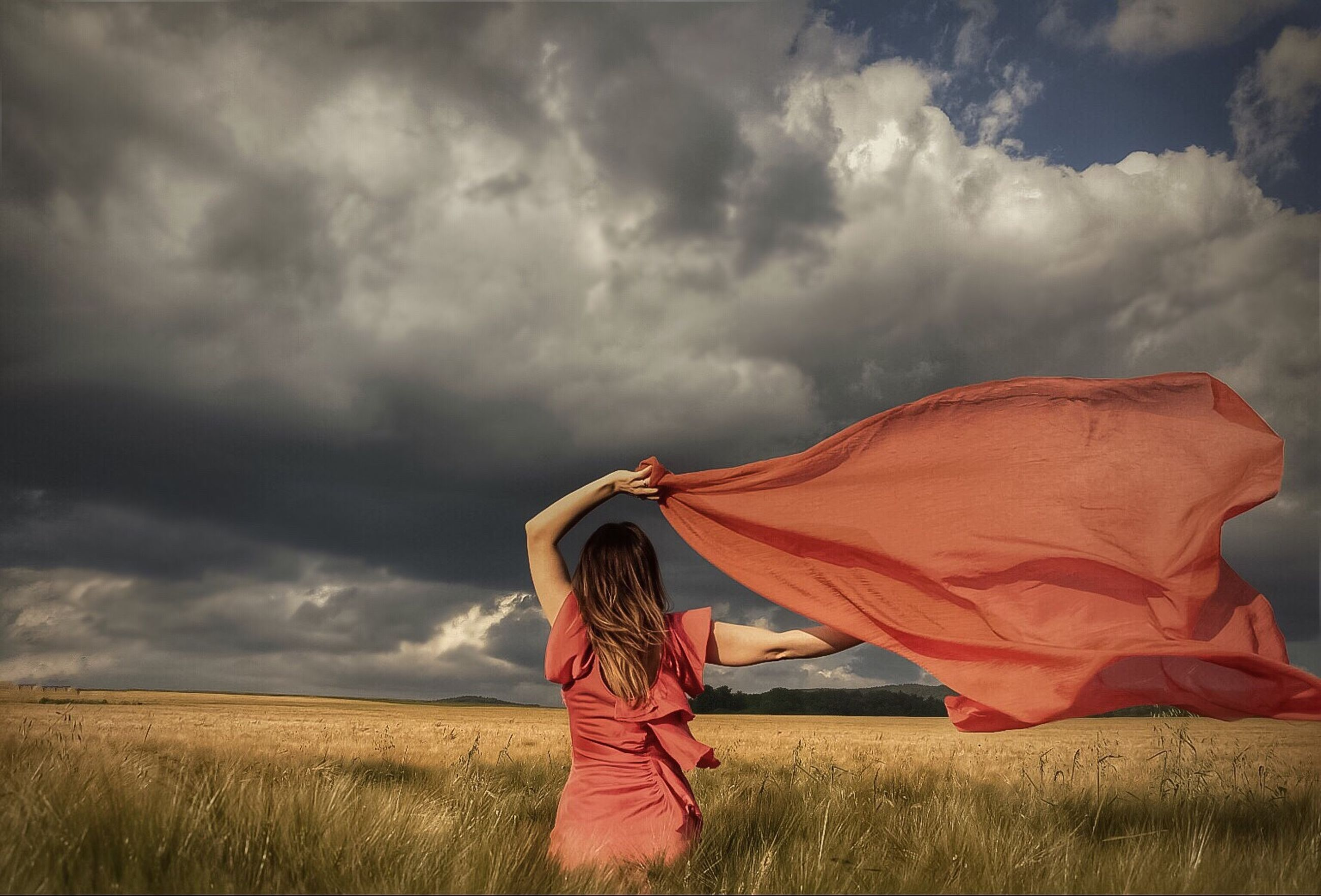 sky, cloud - sky, field, grass, cloudy, lifestyles, leisure activity, landscape, cloud, rear view, red, person, casual clothing, standing, tranquil scene, tranquility, relaxation, overcast