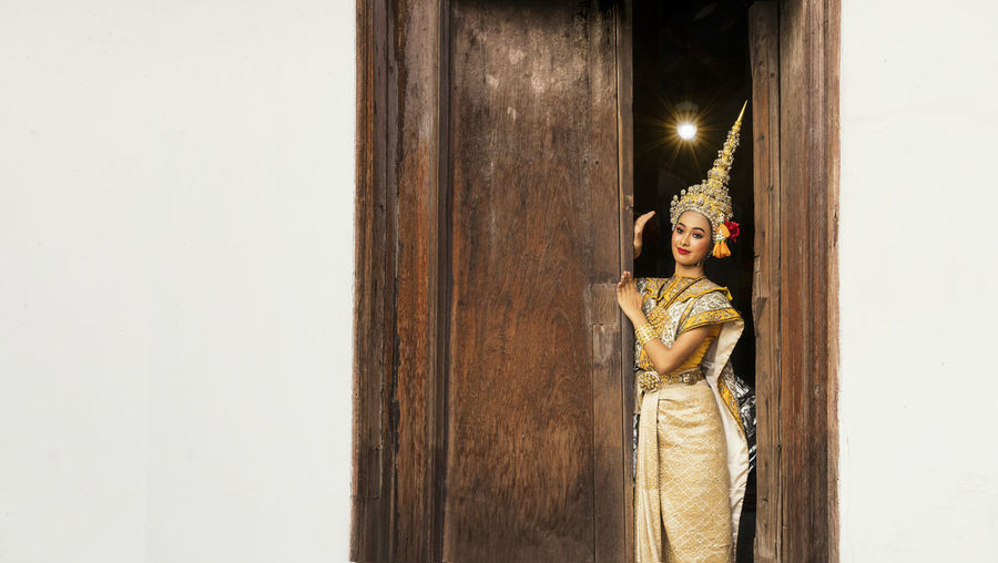 An asian woman wearing a traditional costume for ramya is hidden at the door.
