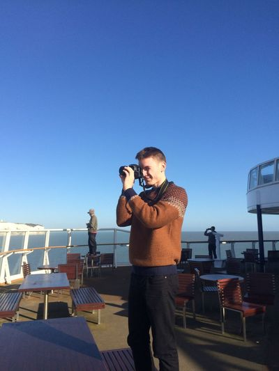 Man Photographing In Ferry Using Camera Against Clear Blue Sky