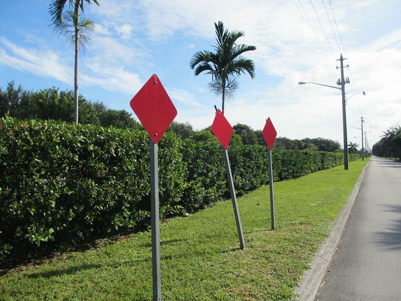 Red Road Signs By Road Against Cloudy Sky On Sunny Day