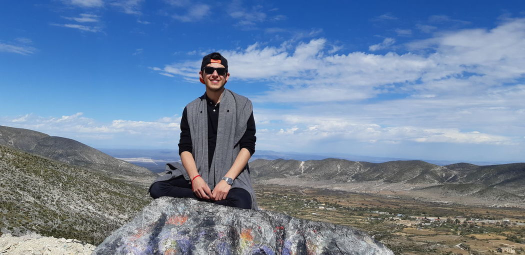 Portrait of smiling man sitting on rock against sky