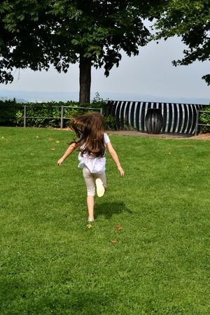Little girl with long hair running in a park From Behind Running Girl Casual Clothing Child Childhood Day Females Field Full Length Girls Grass Green Color Hair Hairstyle Human Arm Land Leisure Activity Lifestyles Long Hair Nature One Person Real People Springtime Tree Women