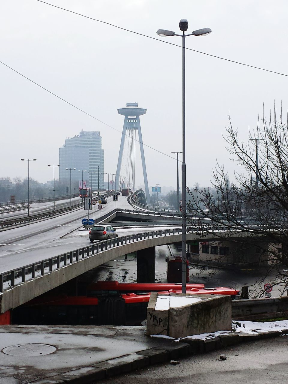 transportation, connection, bridge - man made structure, mode of transport, architecture, built structure, land vehicle, car, outdoors, cable, sky, day, street light, city, suspension bridge, building exterior, bridge, no people, road, tree, electricity pylon, snow, winter, clear sky, nature