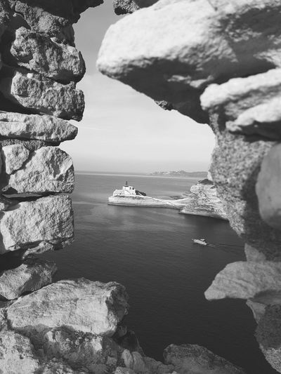 High angle view of ship on sea against sky seen through rock formations