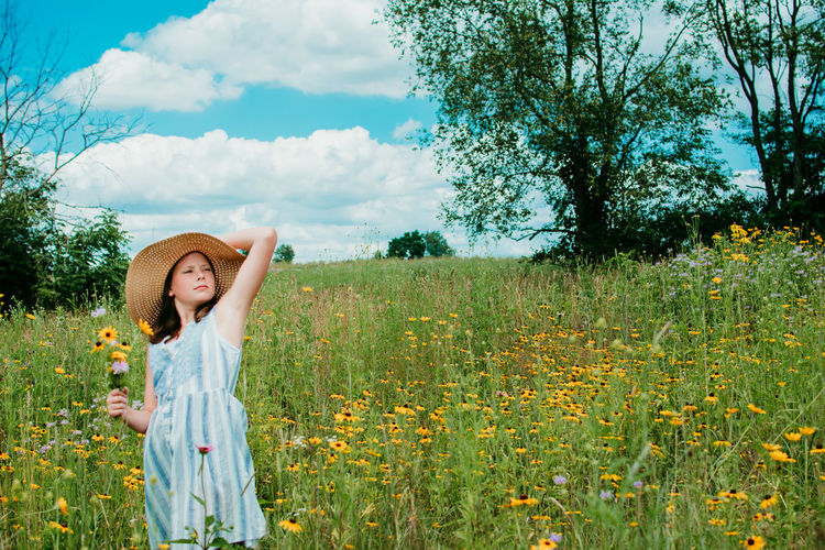 Teen girl standing on grassy field against yellow flowers