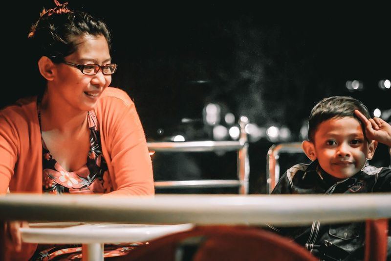 Close-up of mother and son sitting at table in restaurant during night