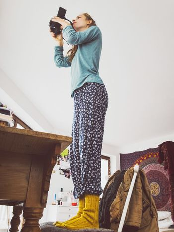 Low Angle View Creative Young Woman Female Photographer Photographer Casual Clothing Casual Look Warm Socks Wool Warm Clothing Home Interior Chair Taking Photo Woman Who Inspire You Woman At Work Home Is Where The Art Is Creative Process Modern Workplace Culture Small Business Heroes