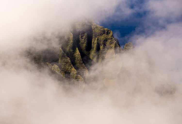 Fluted rocks of the na pali mountains through the clouds from pihea trail near pu'u o kila on kauai