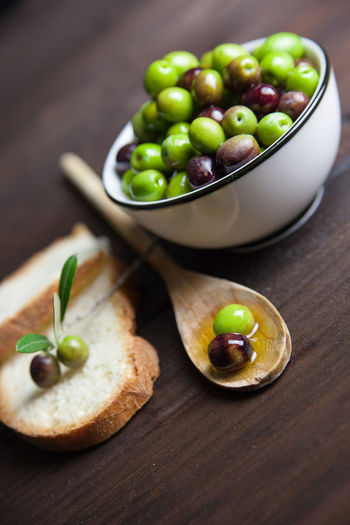 High angle view of green olives and bread on table