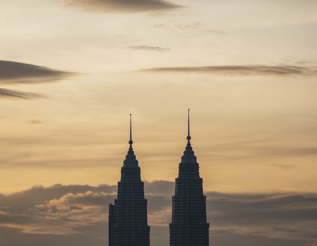 High Section Of Petronas Towers Against Cloudy Sky During Sunset