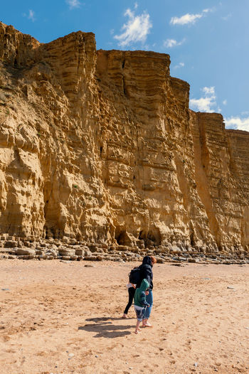 Full length of mother and kids walking on beach against rock formation