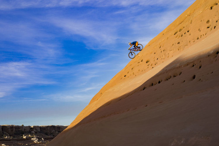 Low angle view of man riding bicycle on rock formation