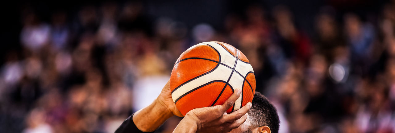 Close-up of hand holding ball against blurred background