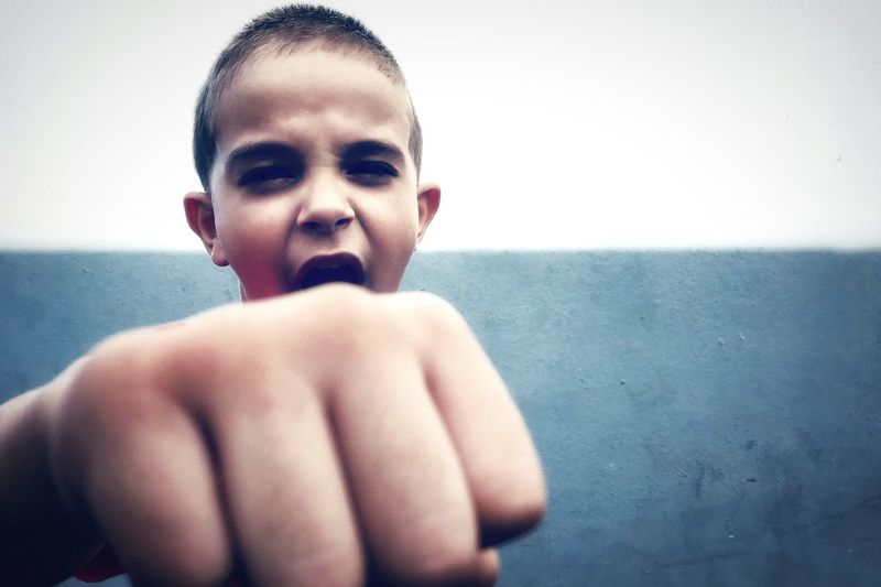 Boy Showing Fist Against Wall