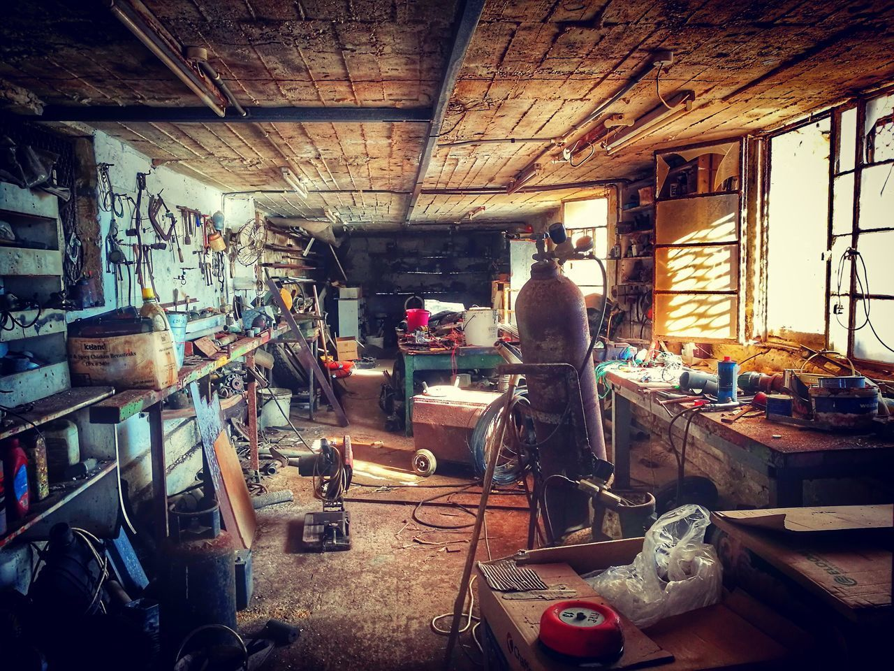indoors, messy, large group of objects, workshop, window, standing, one person, real people, day, table, old, working, domestic room, container, work tool, abandoned, business, kitchen