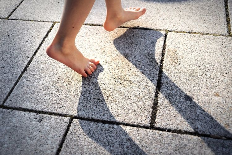 barefoot Body Part Child Childhood City Day Footpath High Angle View Human Body Part Human Foot Human Leg Human Limb Limb Low Section Offspring One Person Outdoors Paving Stone Shadow Street Sunlight