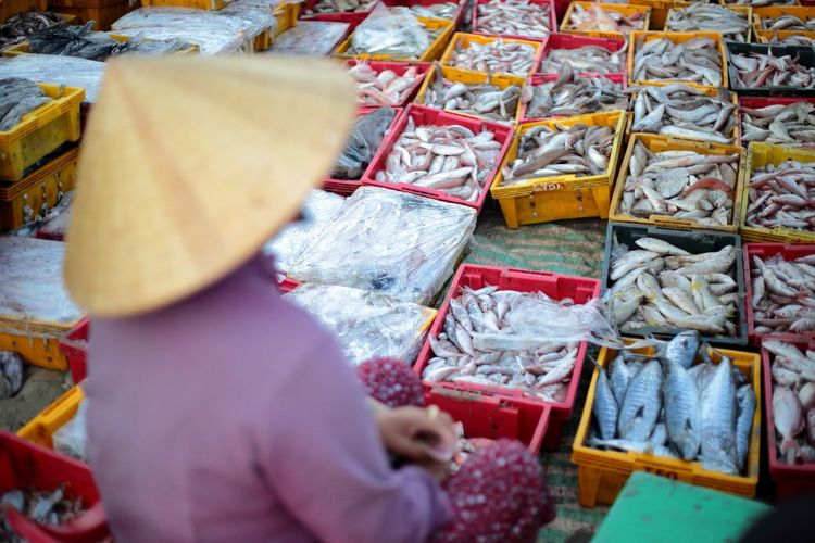 Close-up of person in hat selling fish at market stall