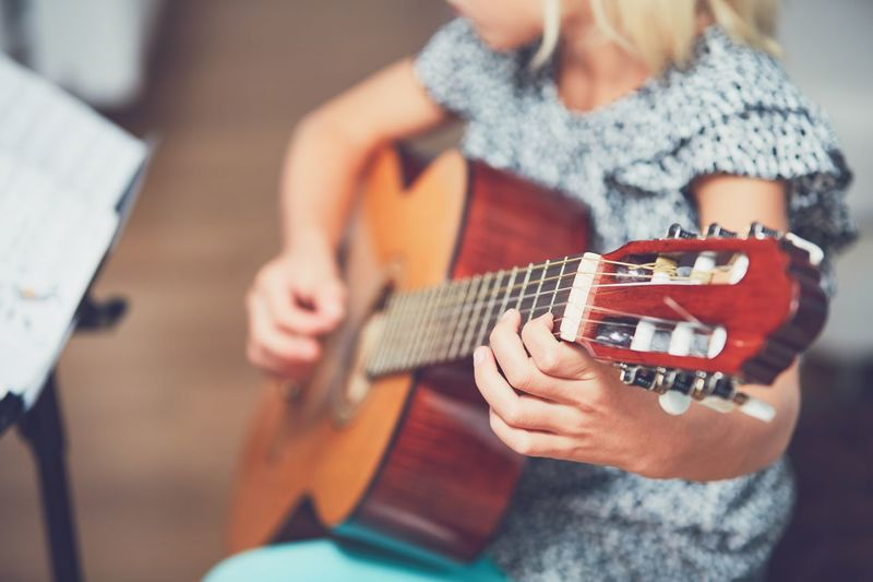 Midsection Of Girl Playing Guitar At Home