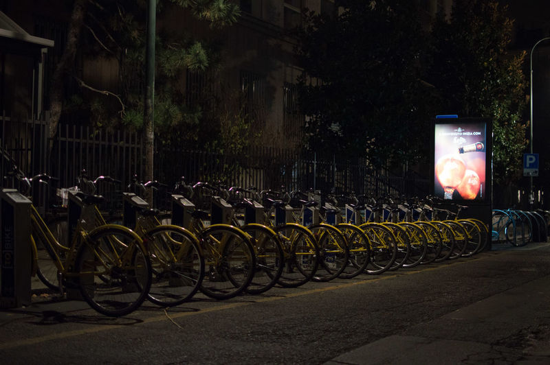 Bicycles parked on road in city at night