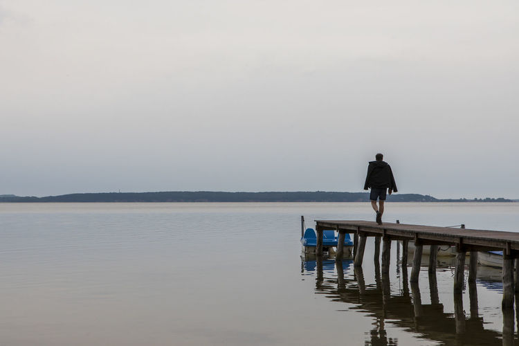 Rear view of man standing on shore against sky