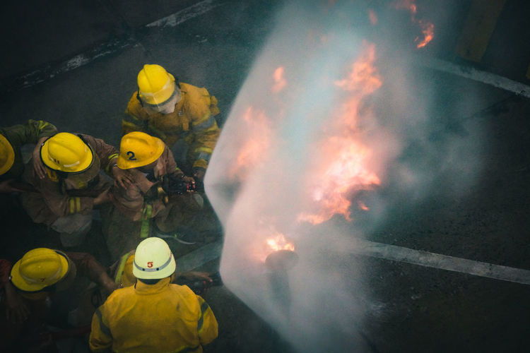 High angle view of firefighters spraying water on fire