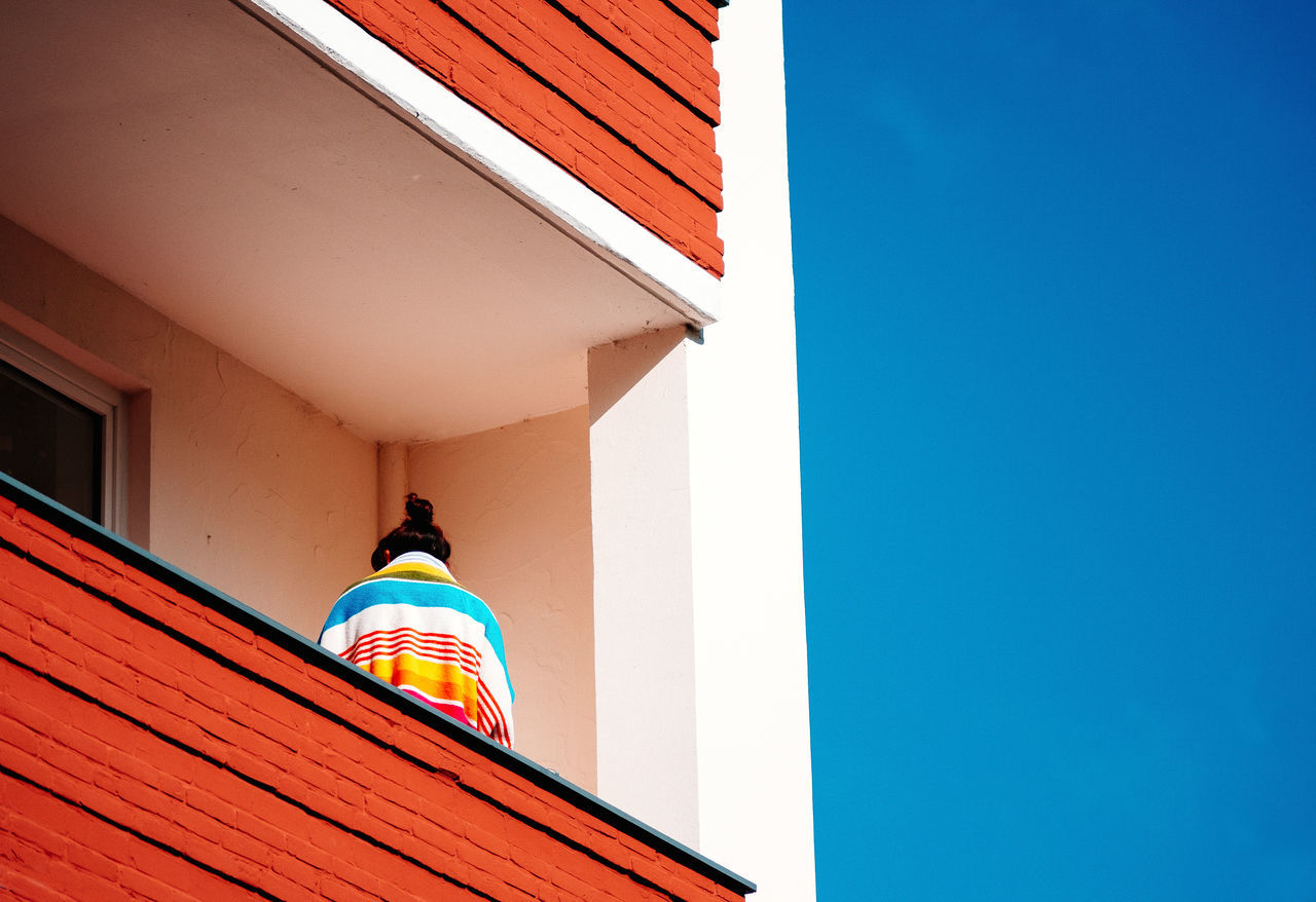 Low angle view of person standing on the balcony of building