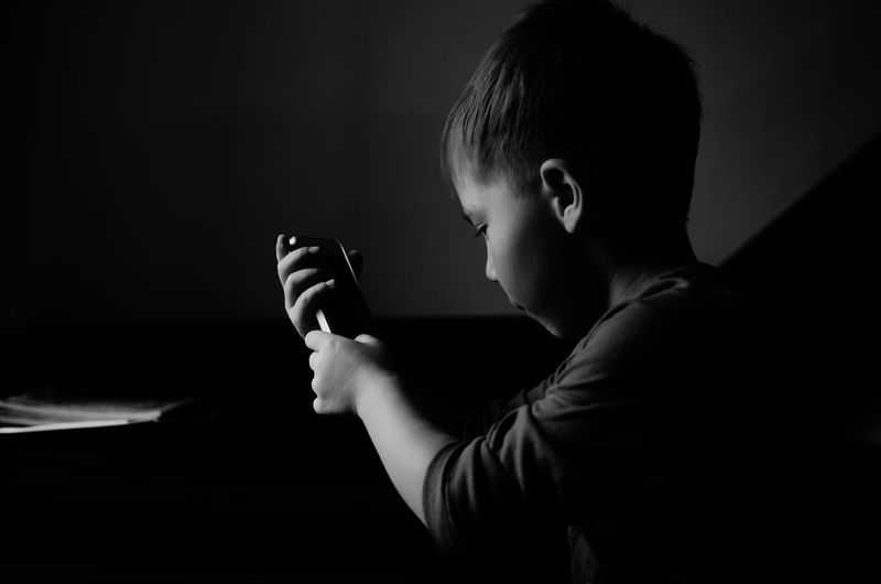 Side view of child playing with smart phone