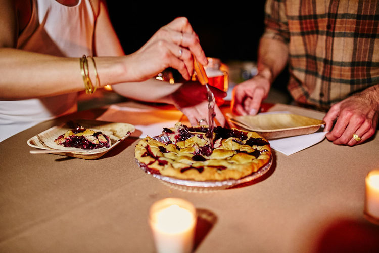Midsection of couple eating tarts on table