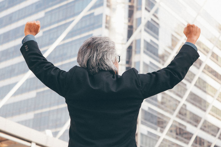 Businessman clenching fists against office building