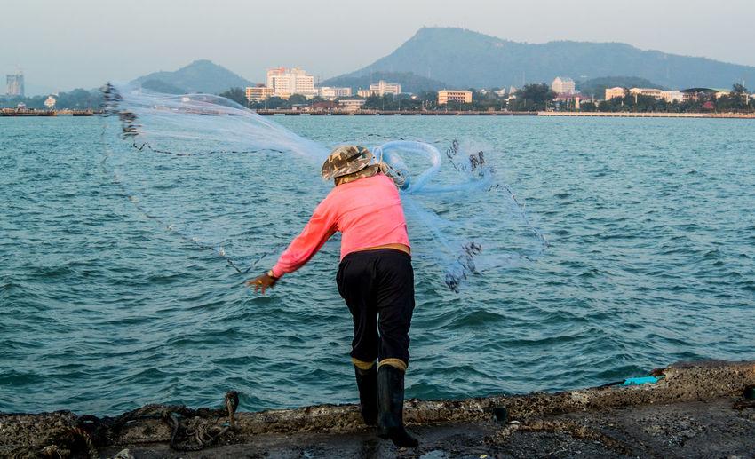 Full length rear view of man throwing fishing net in river