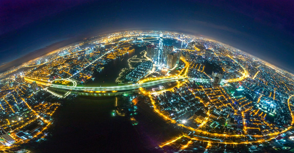 Fish eye view of illuminated cityscape against sky at night