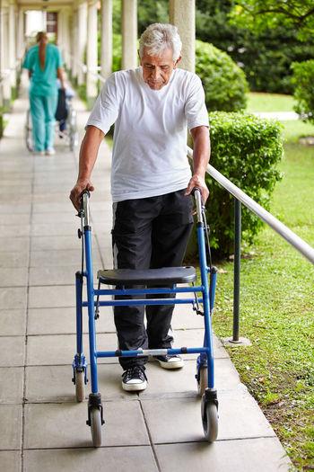 Senior man and nurse walking on walkway