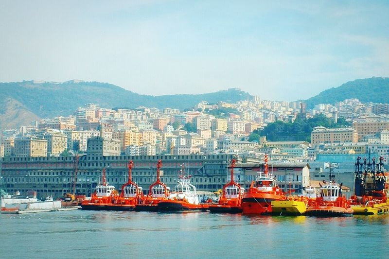 Tugboats Moored At Port Of Genoa Against Sky