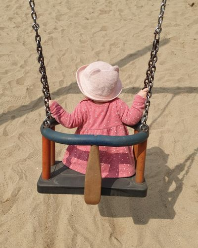 Rear view of girl sitting on swing at playground