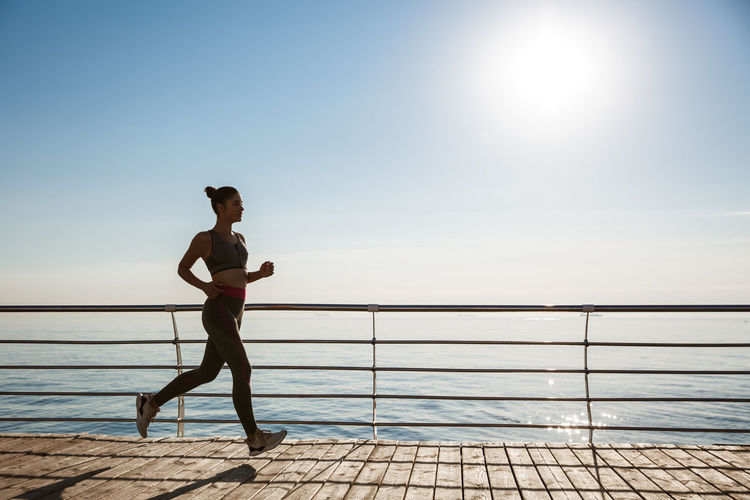 Woman jogging by sea against clear sky