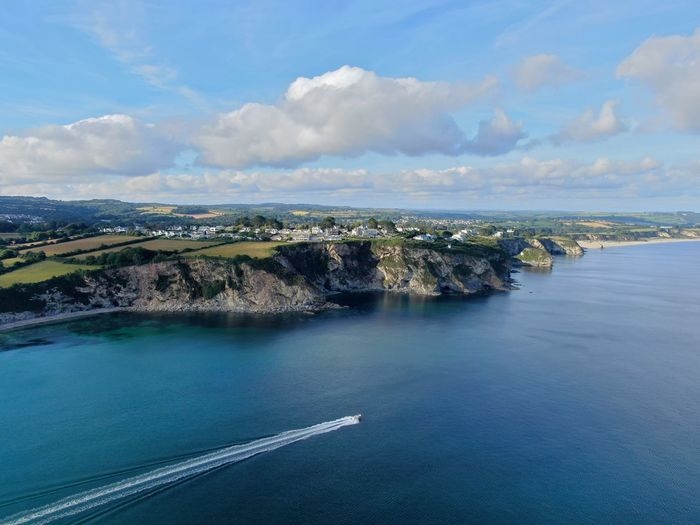 Scenic view of sea at cornwall coastline with cliffs and powerboat