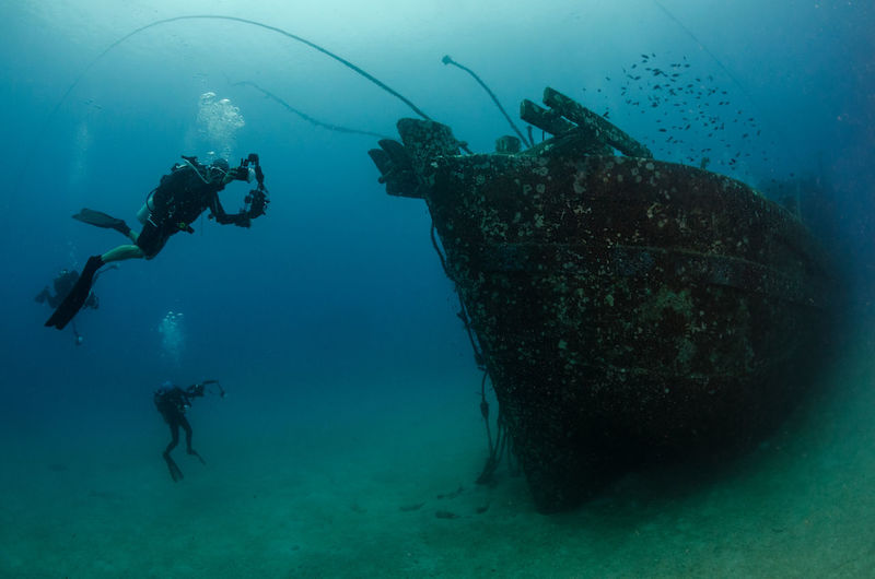 Divers photographing a ship wreck Adventures Ship Wreck Wreck Adventure Animal Themes Blue Day Exploration Malaysia Nature One Person People Photographer Real People Scuba Diver Scuba Diving Sea Sea Life Ship Swimming Tourism UnderSea Underwater Undiscovered Water