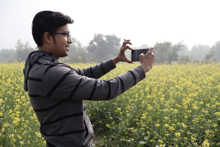 Side view of young man photographing on filed