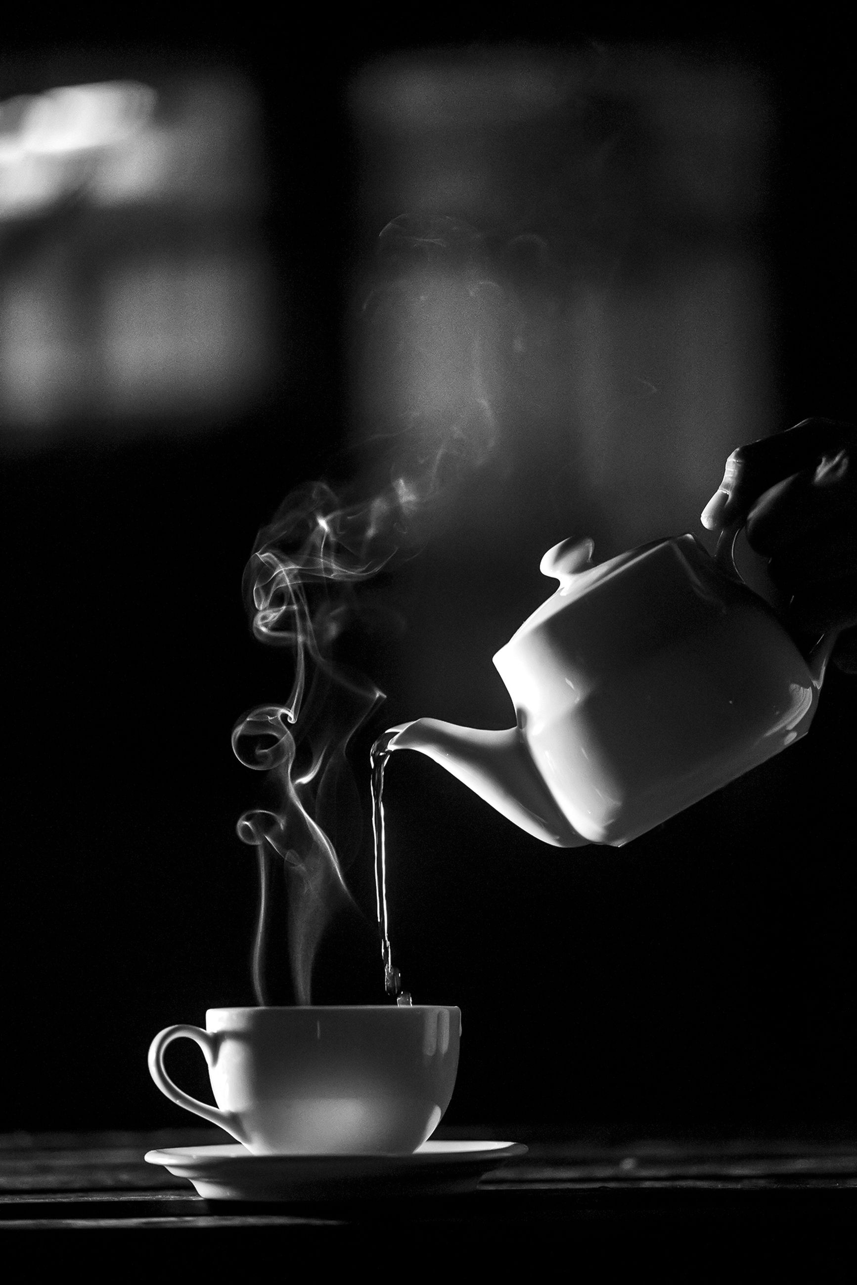 smoke - physical structure, drink, steam, food and drink, indoors, refreshment, heat - temperature, cup, coffee, focus on foreground, motion, mug, coffee - drink, coffee cup, hot drink, social issues, tea, holding, tea - hot drink, preparation, crockery, tea cup