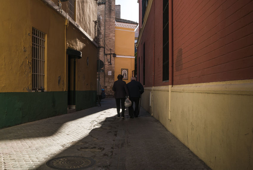 Older couple walking down the street in Seville, Spain Color Couple Daytime Europe Older Couple People People From Behind Real People Rear View S Sevilla Seville Shadow Spa Street Street Photography Streetphotography