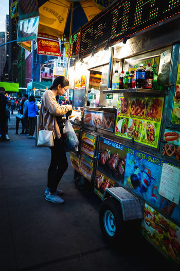 Man standing at illuminated market stall in city