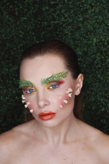 Portrait of beautiful young woman with flower on face outdoors